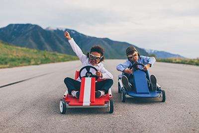 Two children racing on go karts
