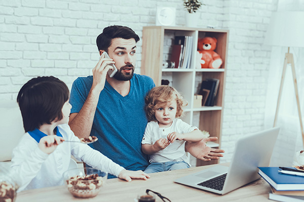 man working from home with children